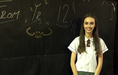 Year 12 student Jessica Murphy standing in front of a blackboard smiling