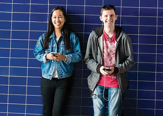 A young male and female stand in front of tiled blue wall and smile to camera; each is holding a smartphone in both hands.