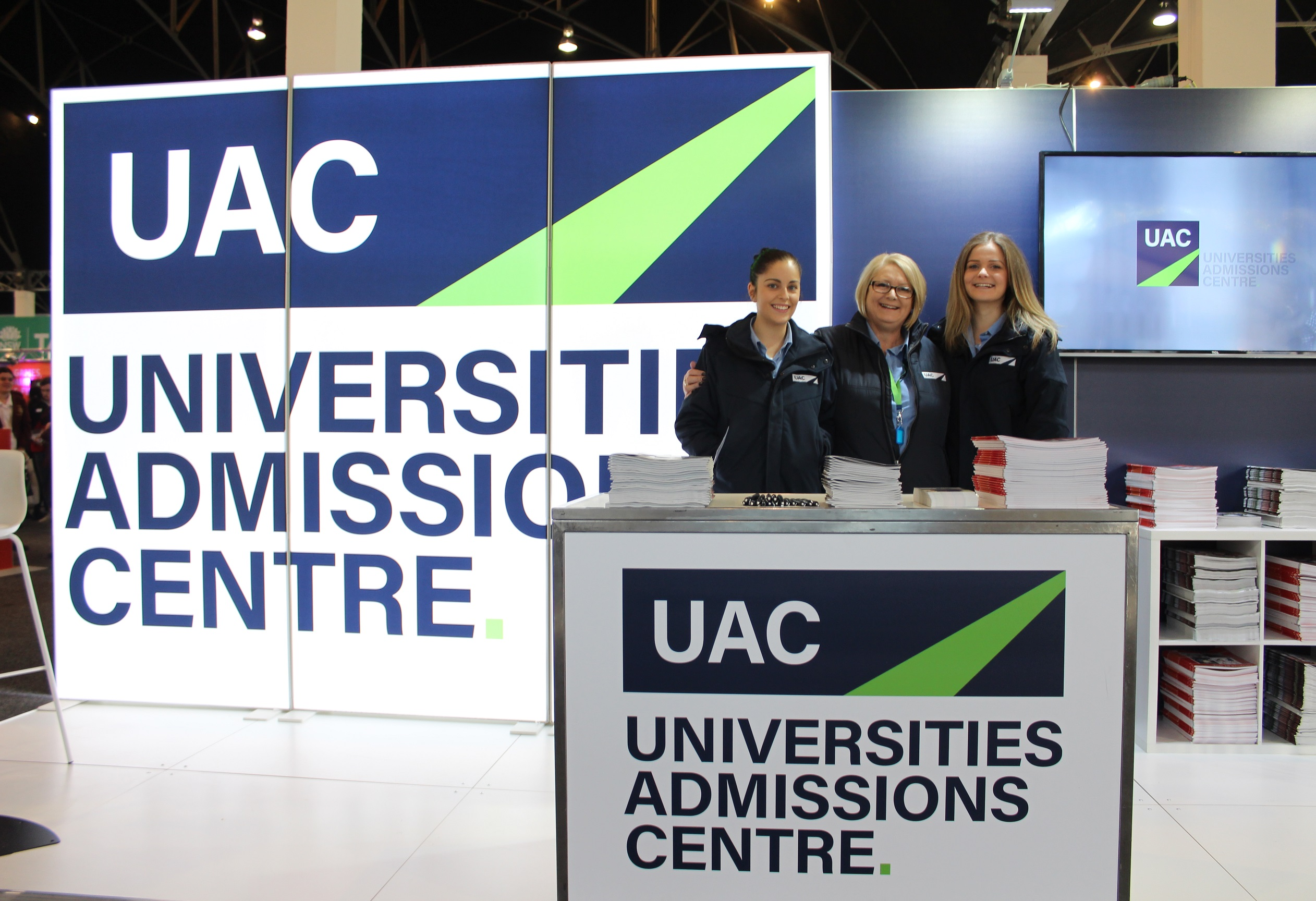 Three female UAC staff members stand smiling to camera at UAC expo stall; stacks of publications fill the stall shelves.