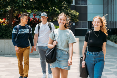 Four young students on campus walking towards camera