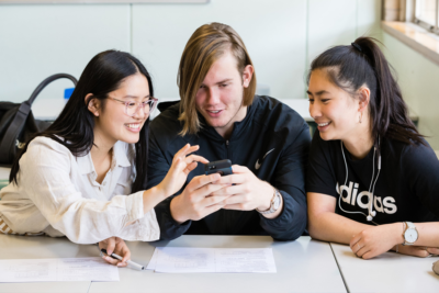 Three young people, a guy and two girls, huddle over a mobile phone smiling
