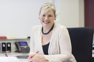 Student of a Masters of Business Psychology, Penny, sitting at a desk, smiling to camera and holding a red pen