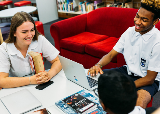 Three high school students working and talking while sitting around a table in a school library
