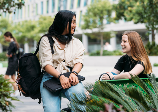 Two smiling female students talk to each other on campus