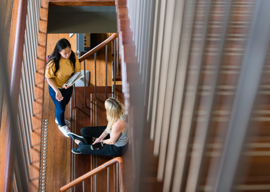 One female student sitting down talking to another female student standing up