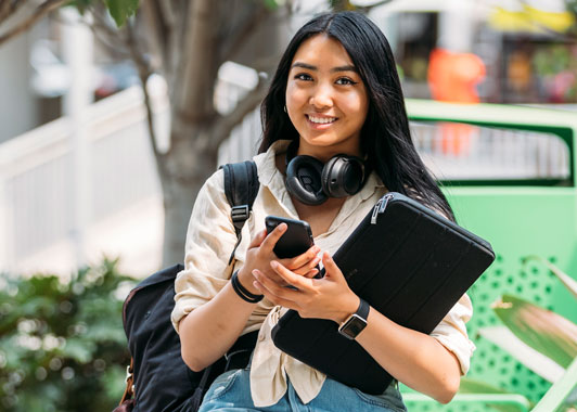 Female uni student holding a laptop and phone smiles to camera