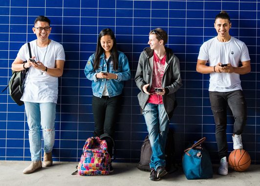 Four smiling young people standing in front of tiled blue wall