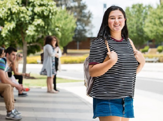 Girl standing outdoors facing camera holding backpack, smiling and wearing striped t-shirt