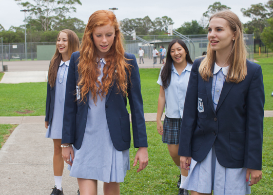 Four female students in school uniform walking outdoors and chatting to one another