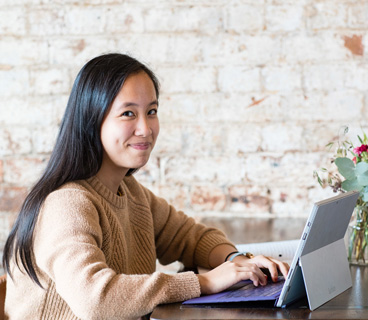Student sitting in front of a laptop smiling to camera