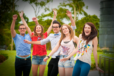 Five young people in colourful clothing gesture energetically to camera outside, with arms in the air