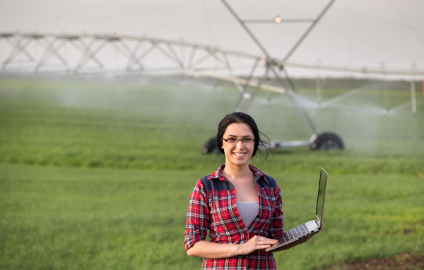 Young woman with laptop outside in check shirt and glasses standing in front of a large irrigation system in a field