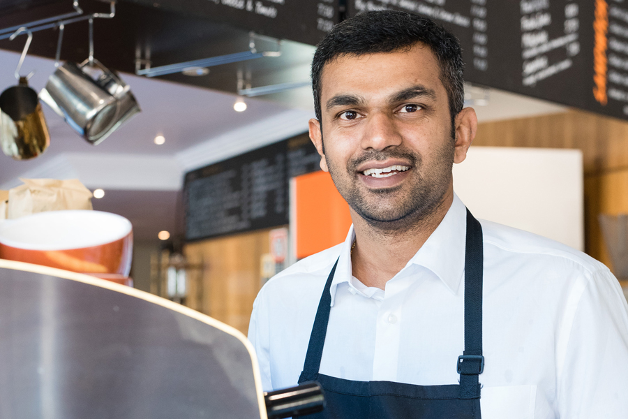 Barista wearing uniform standing in front of coffee machine in a cafe facing camera and smiling