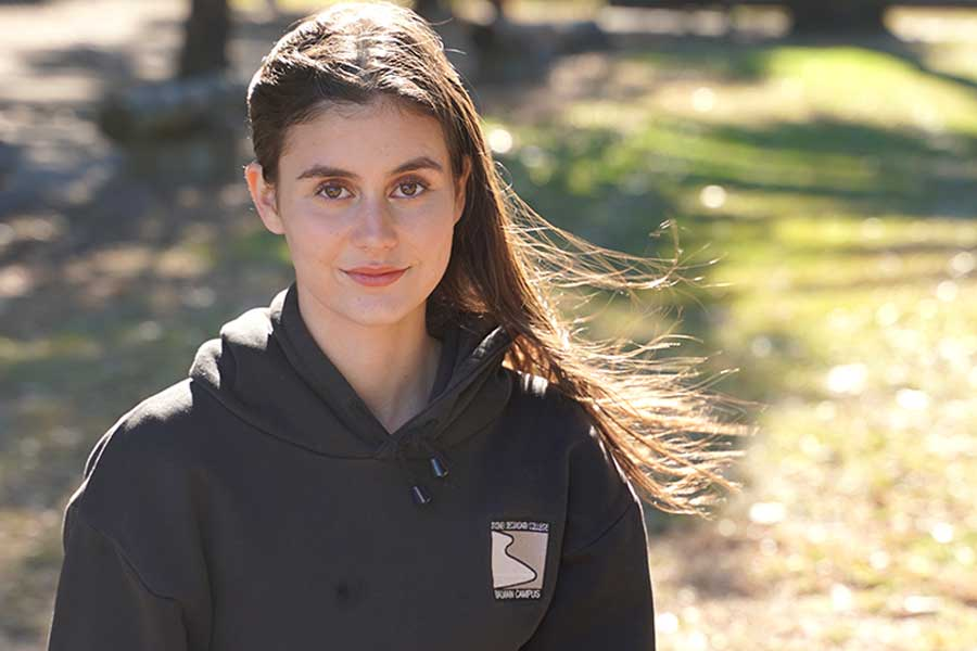 Year 10 student Josie Keevers stands outside wearing black school hoodie and smiles to camera