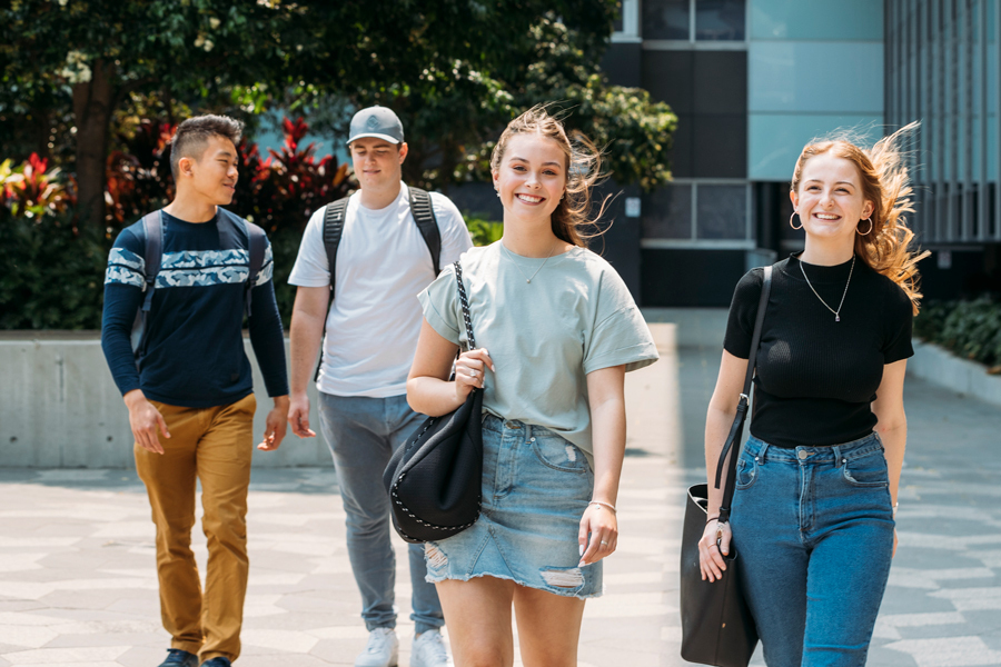 Four young uni students walking towards camera outside