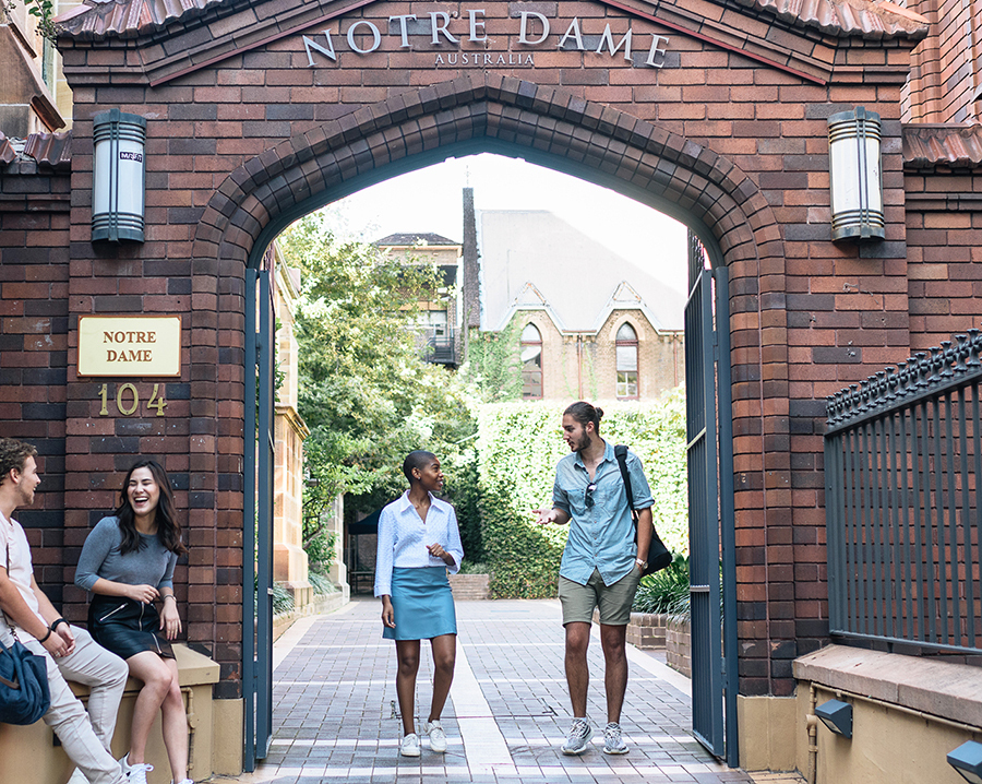 A girl and boy walking through the gate of Notre Dame University, Sydney