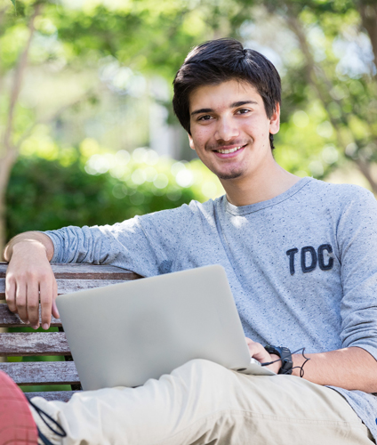 Guy with laptop reclining with one arm resting and legs up on a park bench, smiling to camera